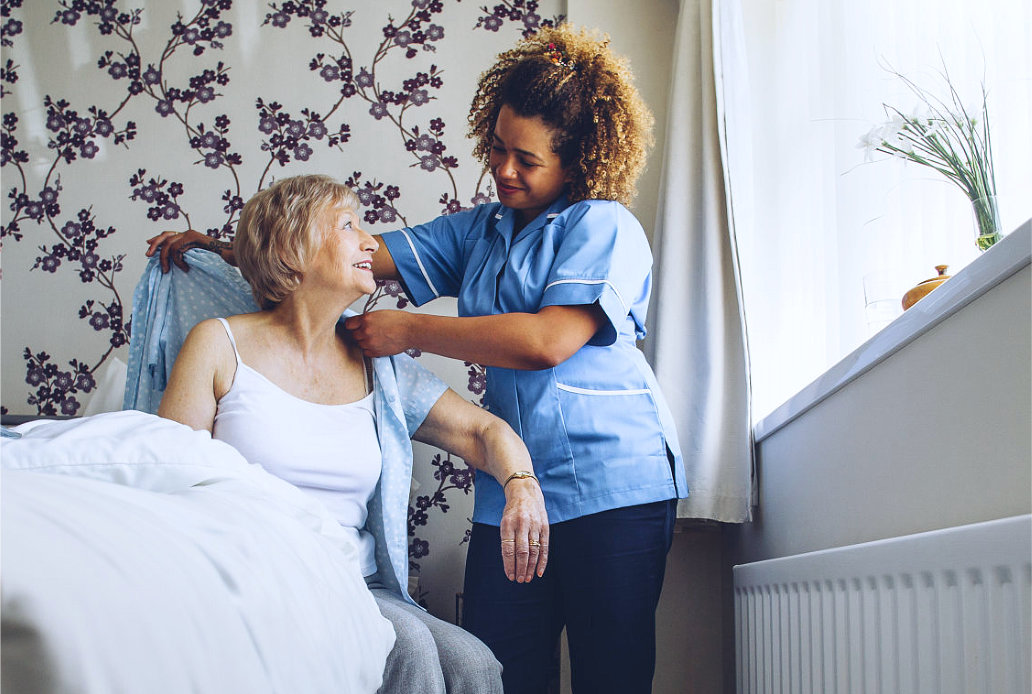 caregiver helping a senior put on clothes