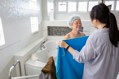 young woman putting towel to a senior woman after bathing