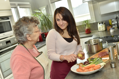 young woman helping a senior prepare food