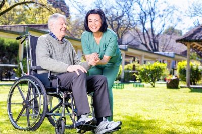 young caregiver holding the hand of her senior patient on a wheelchair