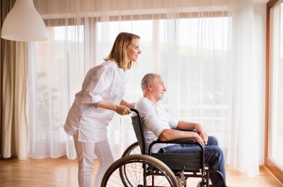 senior man on a wheelchair with his caregiver