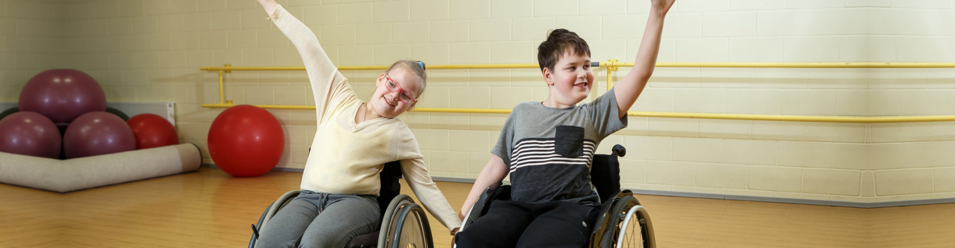 two kids on a wheelchair having fun